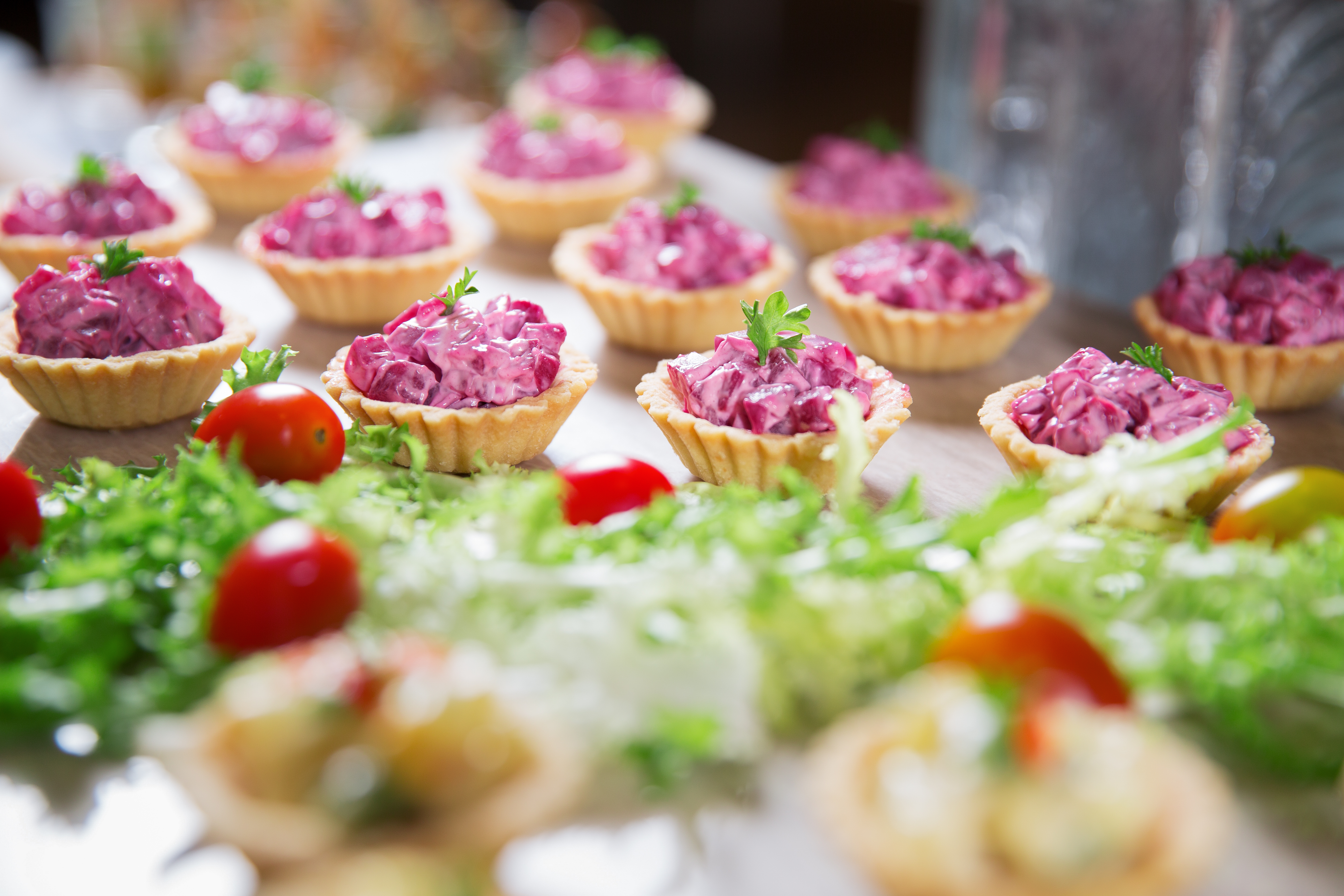 Delicious tartlets stuffed with beetroot salad on buffet table. Catering concept